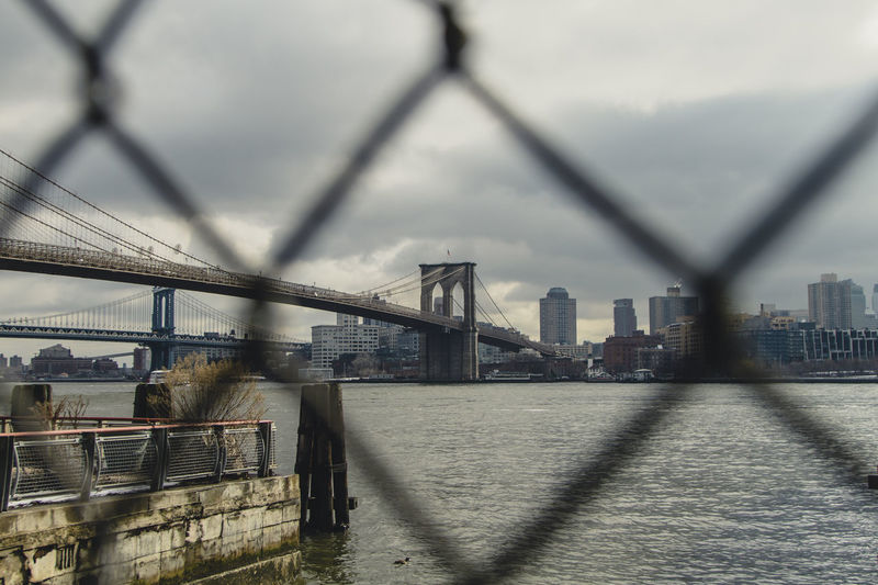 Brooklyn Brooklyn Bridge / New York NYC Architecture Bridge - Man Made Structure Building Exterior Built Structure Chainlink Fence City Cityscape Connection Day No People Outdoors River Sky Skyscraper Suspension Bridge Transportation Travel Destinations Urban Skyline Water
