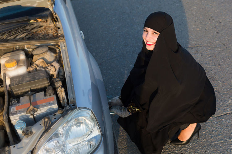 High angle portrait of woman wearing burka repairing vehicle on road