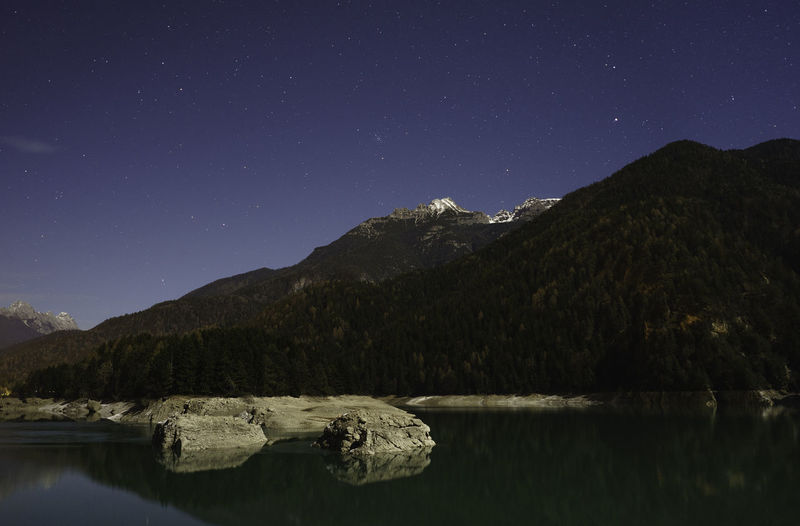 Scenic View Of Lake And Mountains Against Clear Sky At Night