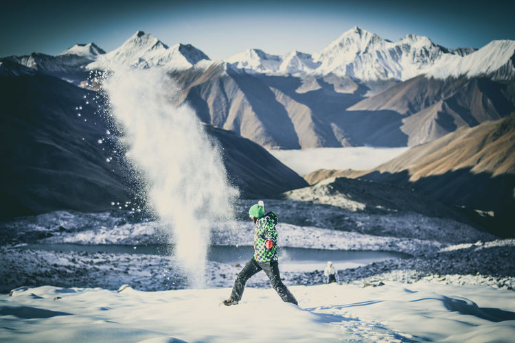 Woman standing on snowcapped mountain