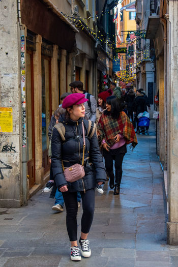 Women walking on street amidst buildings in city