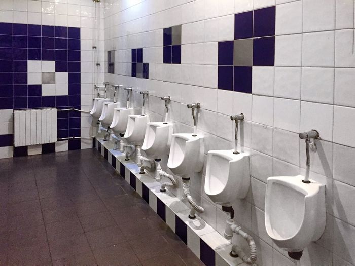 Bathroom Hygiene Tile Toilet Indoors  Public Building Flooring In A Row Public Restroom Repetition White Color Wall - Building Feature No People Domestic Bathroom Urinal Tiled Floor Absence Order Side By Side Mirror