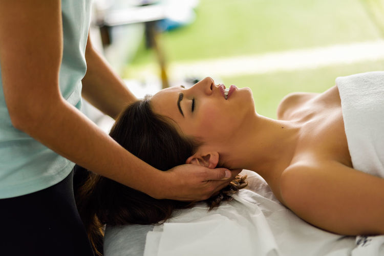 Young caucasian smiling woman receiving a head massage in a spa center with eyes closed. Female patient is receiving treatment by professional therapist. Relaxing Woman Beautiful Woman Beauty Female Girl Head Massage Massage Physiotherapy Relax Spa Center Young Adult Young Woman Young Women