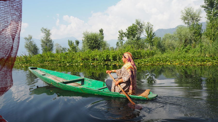 Dal lake local people use Shikara a small boat for transportation in Dal lake a famous tourist attraction of Srinagar Jammu and Kashmir state India Dal Lake Kashmir Animal Themes Beauty In Nature Boat Cloud - Sky Day Full Length Green Color Growth House Boats Lake Mammal Mountain Nature Outdoors People Real People River Shikara Shikara Boat Sky Togetherness Tree Water Young Adult