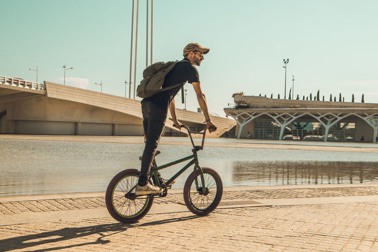 Man riding bicycle on bridge in city against sky
