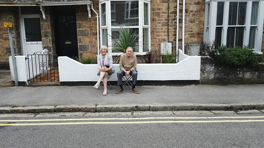 Couple sitting waiting by the side of the road on the pavement Two People Togetherness Heterosexual Couple Couple Men Adults Only Couple - Relationship Bonding Lifestyles Adult Outdoors Friendship Women Real People Connection Full Length People Young Adult Day