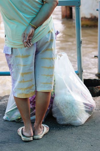 Low Section Of Man With Plastic Bags At Harbor