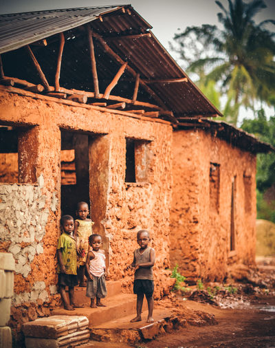 Africa Architecture Building Exterior Casual Clothing Child Children Day Girls Lifestyles Looking Palm Trees Red Soil Road Rural School Travelling Vacation Village Zanzibar
