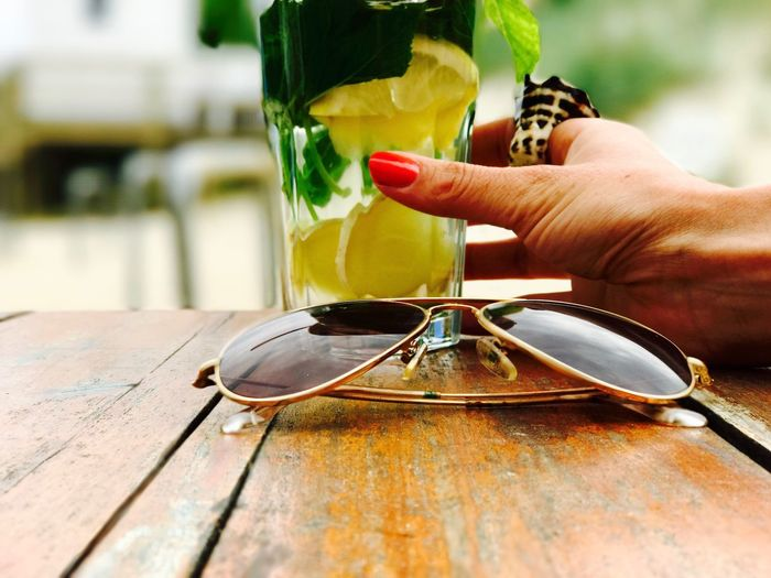 Cropped Hand Of Woman Holding Drink At Wooden Table