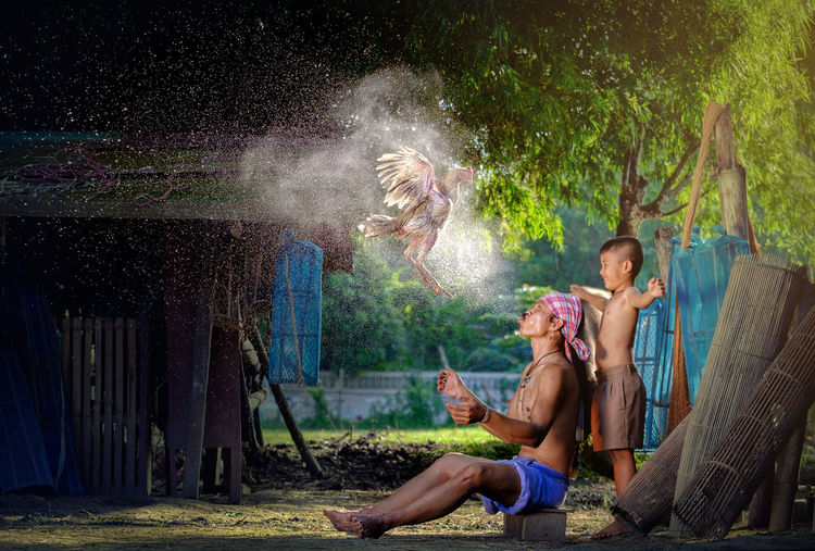 Side View Of Boy Standing By Father Spraying Water On Hen In Village