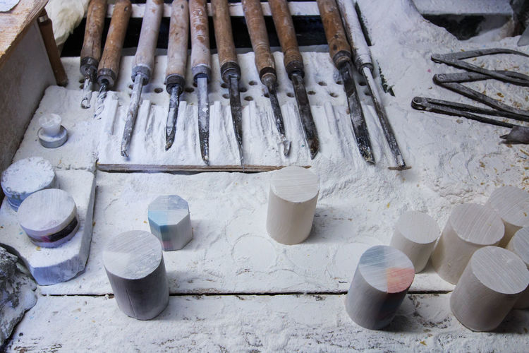 High angle view of alabaster and tools on table at workshop