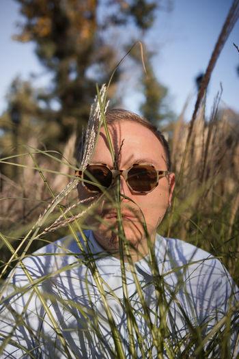 Portrait of man on plant in field