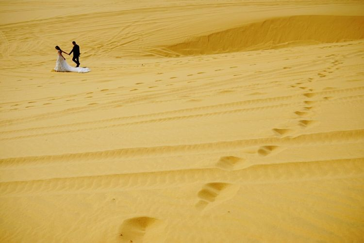 Distant View Of Bride And Groom Walking While Holding Hands At Desert