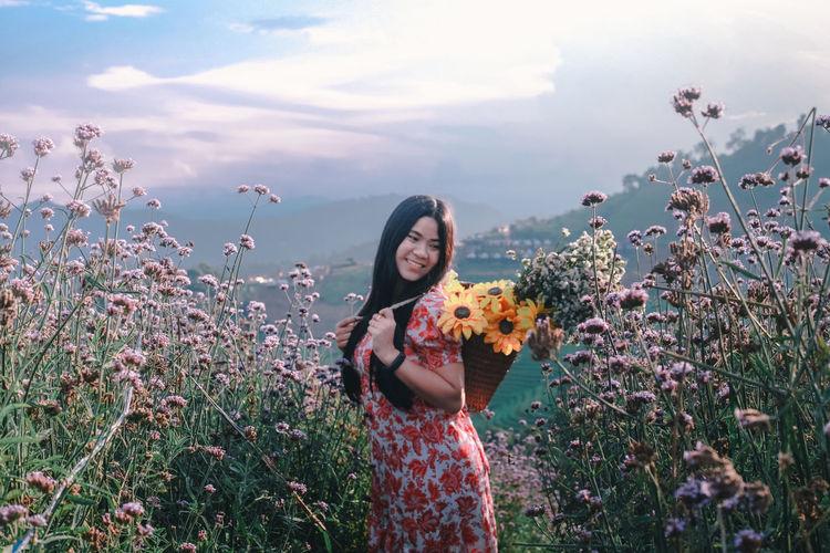 Woman standing by flowering plants against sky