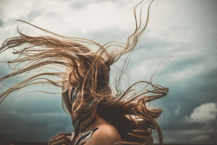 Woman with face paint and tousled hairs standing against cloudy sky