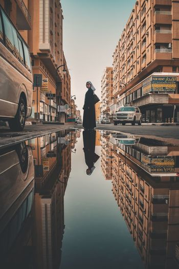 Woman Reflecting On Puddle Amidst Buildings In City