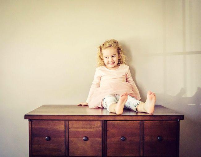 Cute baby girl sitting on sofa