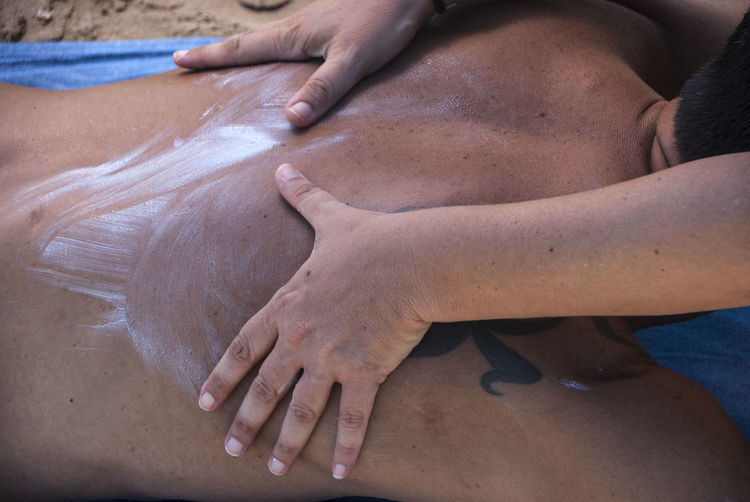 Cropped hand of person applying lotion on man back lying at beach