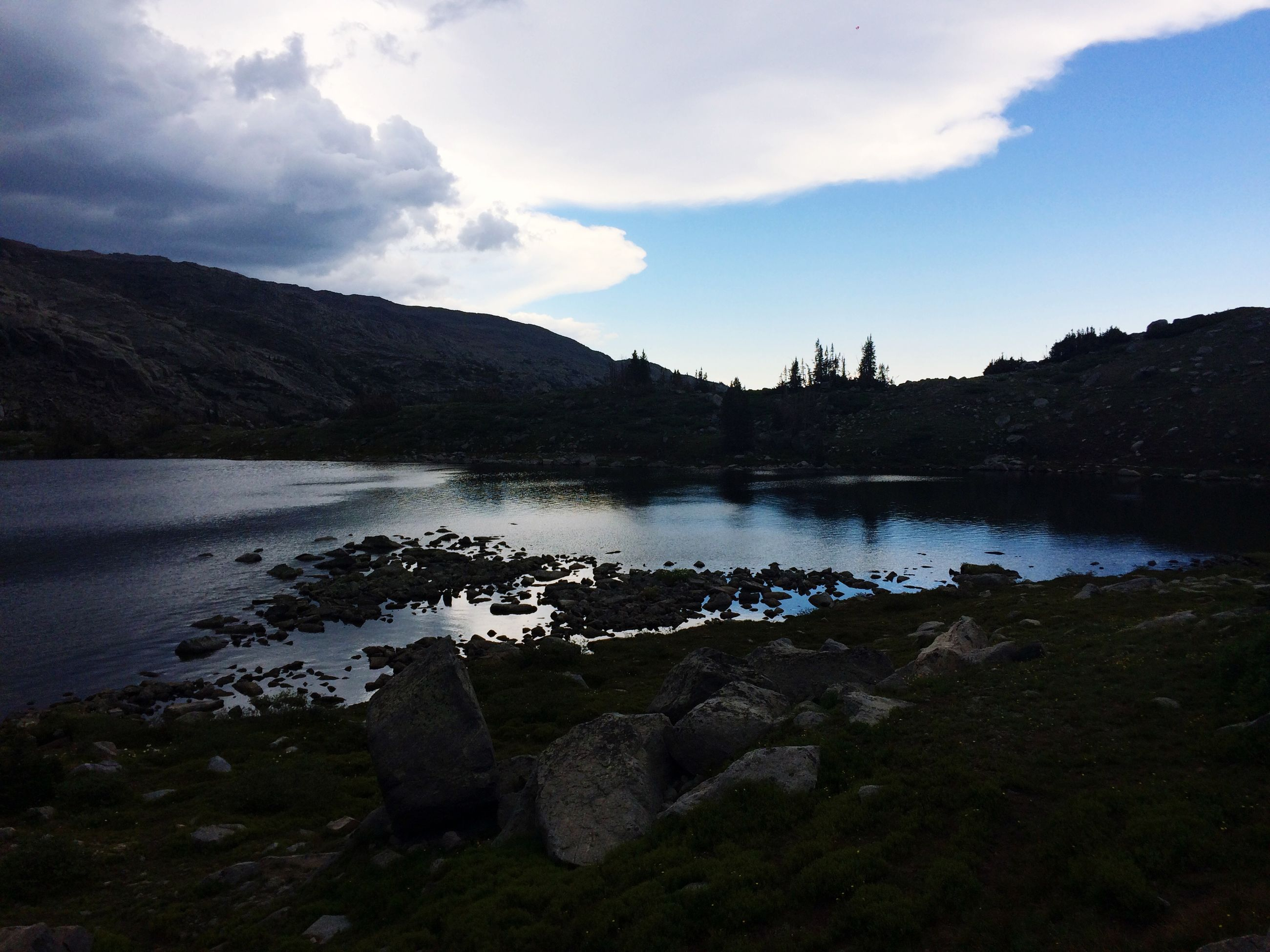 water, sky, tranquil scene, tranquility, lake, mountain, scenics, reflection, beauty in nature, cloud - sky, rock - object, nature, cloud, river, non-urban scene, mountain range, lakeshore, idyllic, landscape, outdoors