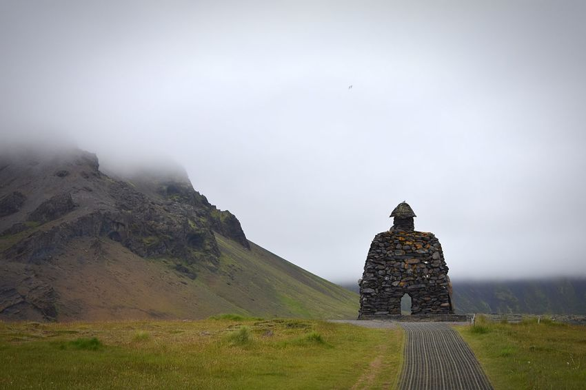 Stone structure with cloudy mountain background Distance Structure Built Statue Material Stone Iceland Town Tourism Built Structure Sky Architecture Fog Building Exterior Travel Destinations History The Past Travel Nature No People Building Tourism Scenics - Nature Mountain Outdoors