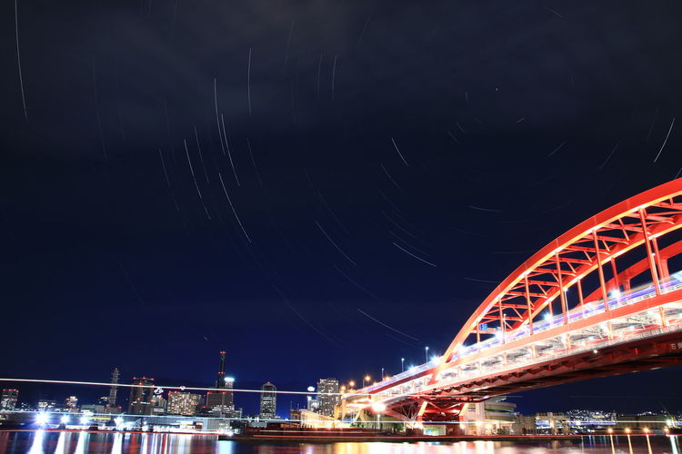 Low Angle View Of Illuminated Bridge Against Sky With Star Trails