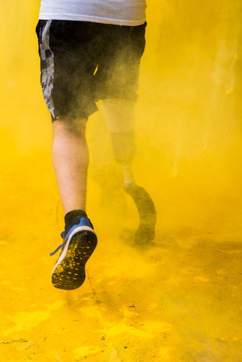 Low section of man with prosthetic leg in yellow powder paint