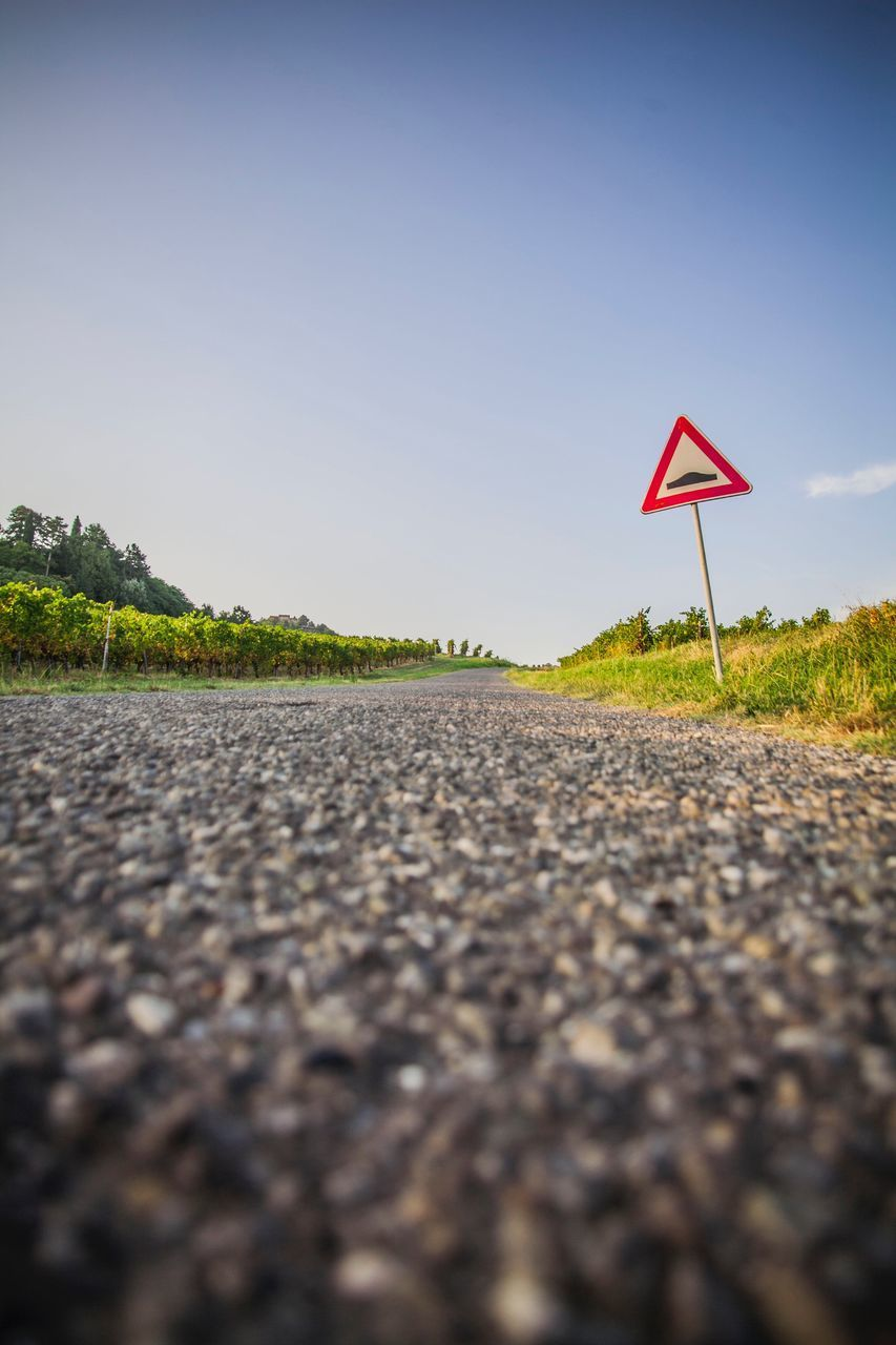 road, sign, transportation, road sign, communication, day, nature, symbol, direction, no people, sky, selective focus, asphalt, surface level, focus on background, outdoors, city, clear sky, warning sign, the way forward