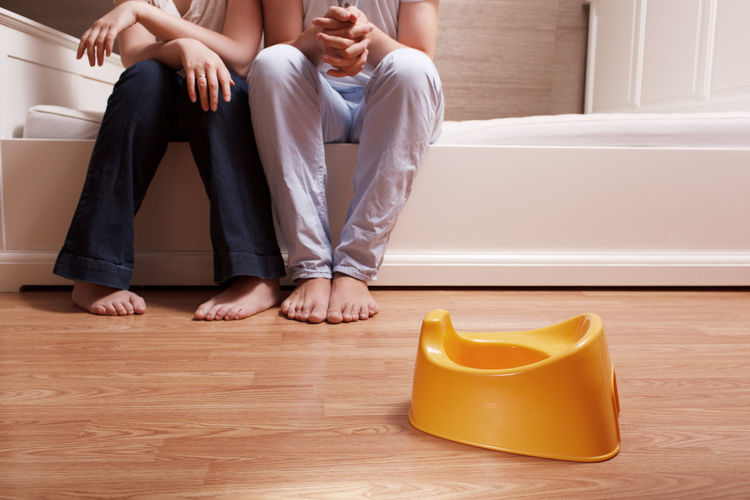 Low section of man and woman sitting on bed in front of yellow toilet bowl