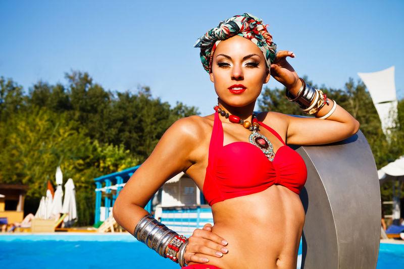 Portrait of young woman in bikini against swimming pool