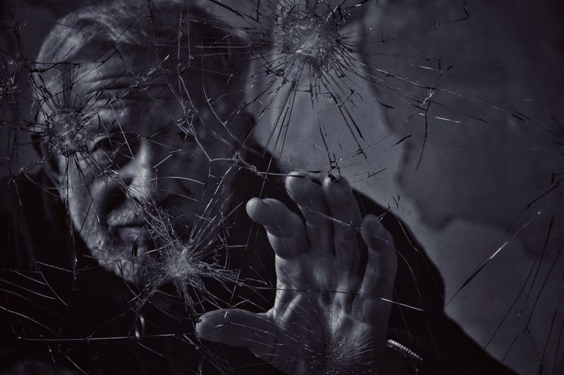 Mature man seen through cracked glass