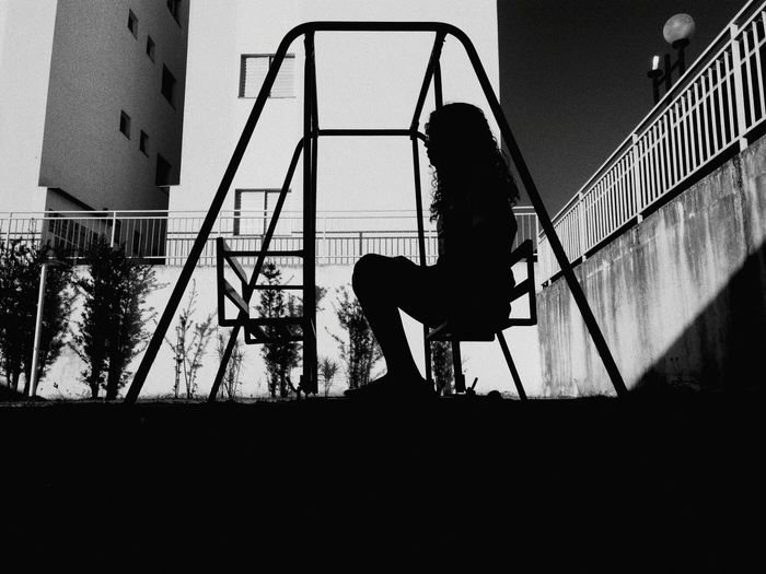 Silhouette Woman Sitting On Seat At Playground