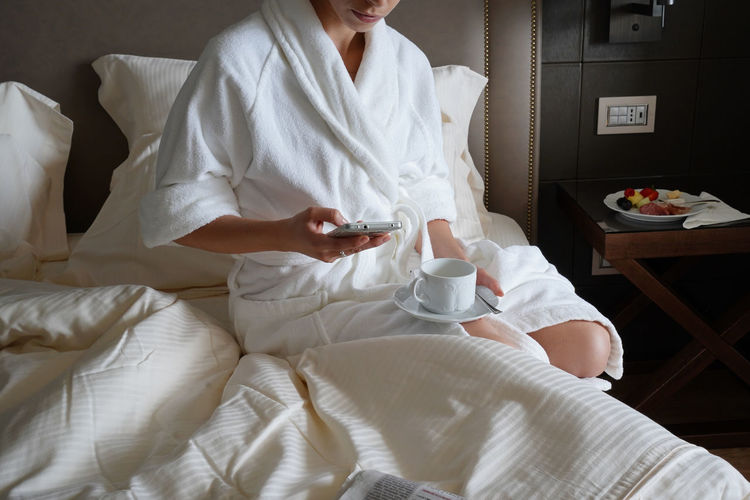 Midsection of woman holding mobile phone while sitting on bed