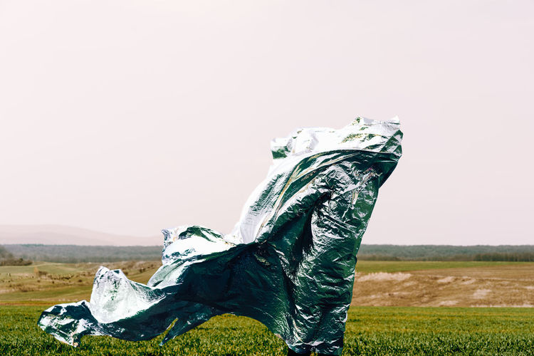 Side view of person with shiny foil on field against clear sky
