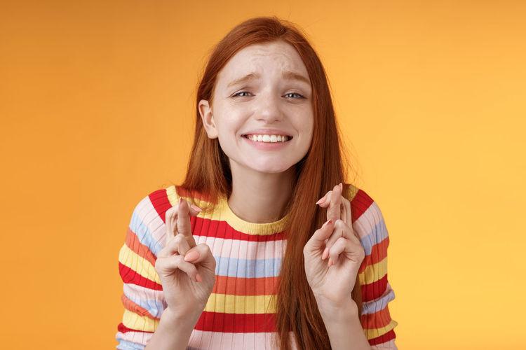 Portrait of smiling boy against orange background