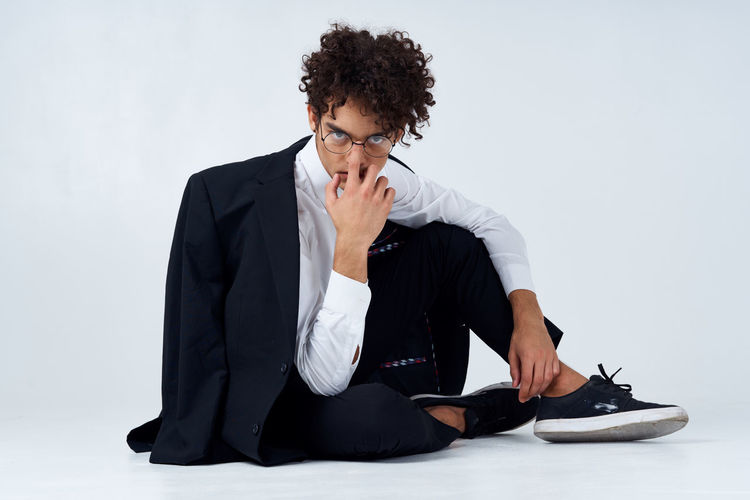Young man sitting on wall against white background