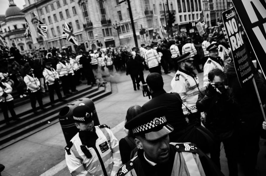 Refugees Welcome Here Demo, Mar 19 2016, Piccadilly Circus. Police setup two lines of defence to guard British nationalists from protesters. Photojournalism Demonstration Leicacamera London Monochrome Streetphoto Refugees Refugeeswelcome Street Photography Londonstreets Maxgor.com Rawstreets Leicaxvario Maxgor Streetphotography Protest Demo Black & White The Photojournalist - 2016 EyeEm Awards Monochrome Photography