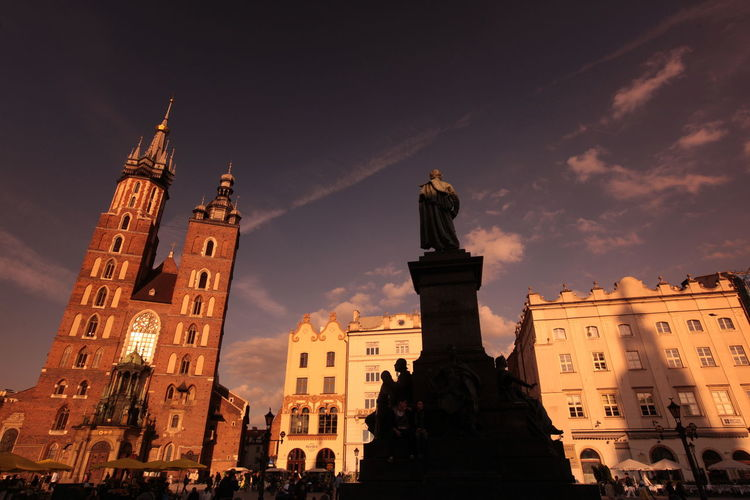 Low Angle View Of Adam Mickiewicz Monument With St Mary Basilica Against Sky