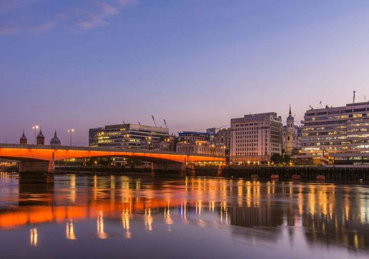 Illuminated city by river against sky at sunset