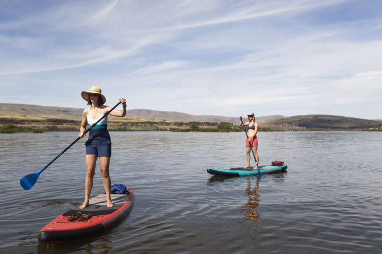 Women on boat in lake against sky
