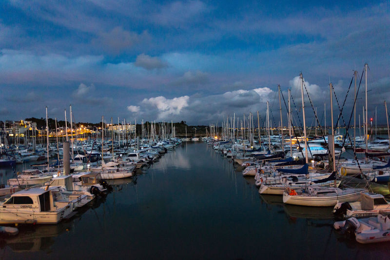 Sailboats moored at harbor against cloudy sky
