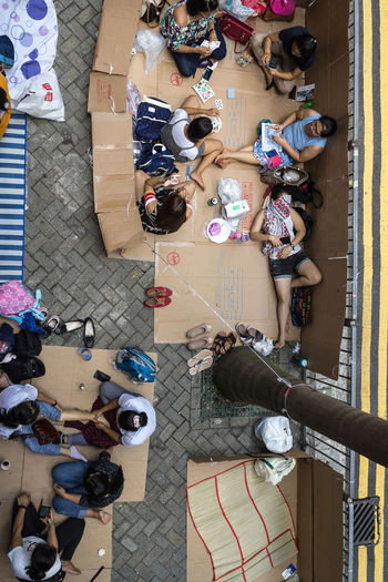 """The photography plan for the """"Sunday life of the domestic helpers"""", the idea is from the lawmaker Yuen Hoi Yung's criticized of street occupied in the Legislative Council on May 23, 2018 by the domestic helpers, which affecting the daily life of Hong Kong people. According to the Employment Ordinance of the Hong Kong Immigration Department, domestic workers are entitled to a statutory """"day off"""" of not less than one day for every seven working than 370,000 foreign domestic helpers in Hong Kong have left their hometowns to work in Hong series of photographs was taken from Central Hong Kong's bustling commercial plan was one shooting process was conducted in a manner that did not disturb the activities of the photos were shot in a sneak composition was shot in three viewing angles such as high altitude and horizontal shooting and a low level of shows how the domestic helpers use every inch of the public areas like pedestrian roads and footbridges for Sunday their have become a unique cultural scene on the streets of Hong Kong. Footbridge Gathering Hong Kong The Street Photographer - 2018 EyeEm Awards Womenaroundtheworld Day Domestic Helper Group Of People Homesick  Hongkongstreet Leisure Activity Lifestyles Outdoor Streetlife Streetphotography Women"""