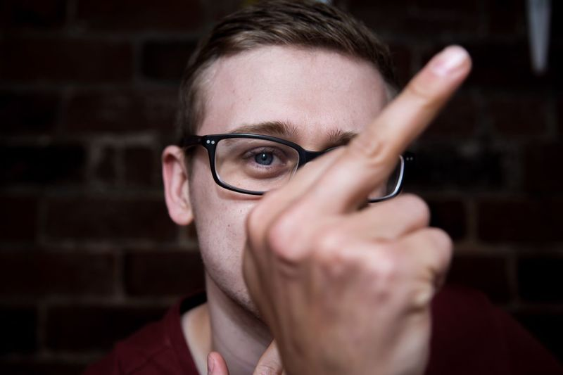 Close-up portrait of man showing obscene gesture against brick wall