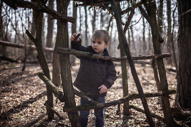 Boy standing by tree in forest