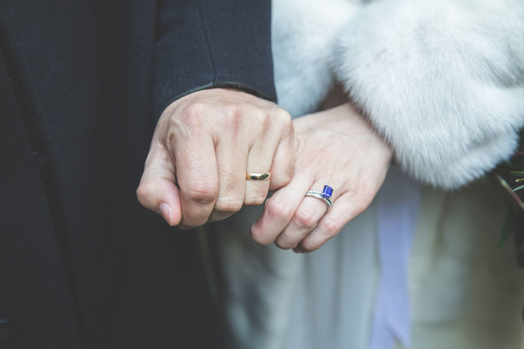 Midsection of bride and groom showing wedding rings