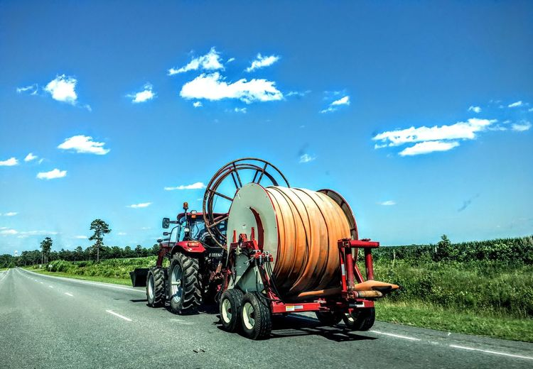 Tractor carrying cable spool on road against sky