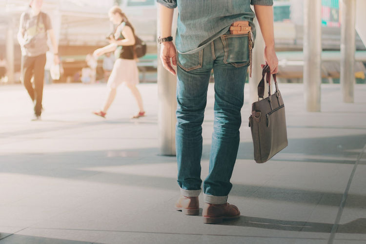Low section of woman holding purse while standing in city