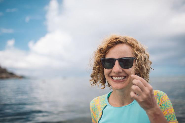 Portrait of smiling man wearing sunglasses against sea