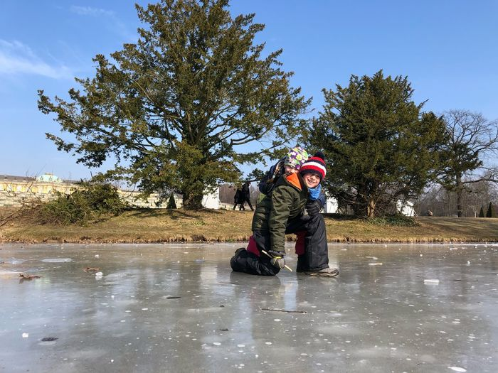 Portrait Of Smiling Brothers On Frozen Lake Against Trees
