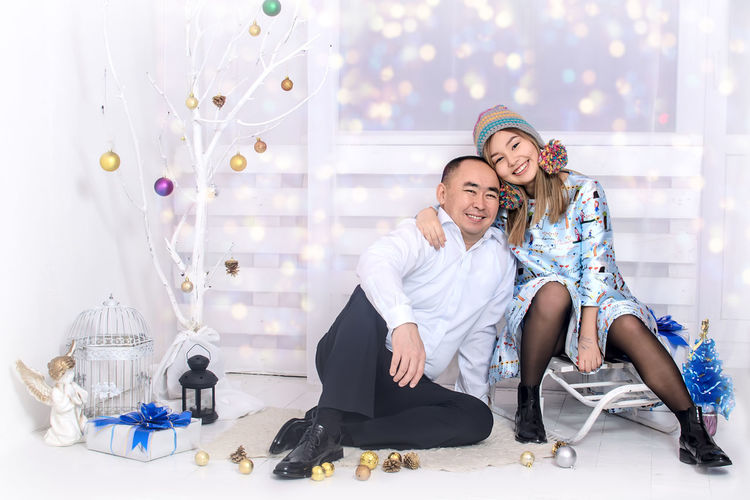 Portrait of happy father with daughter by artificial christmas tree on floor