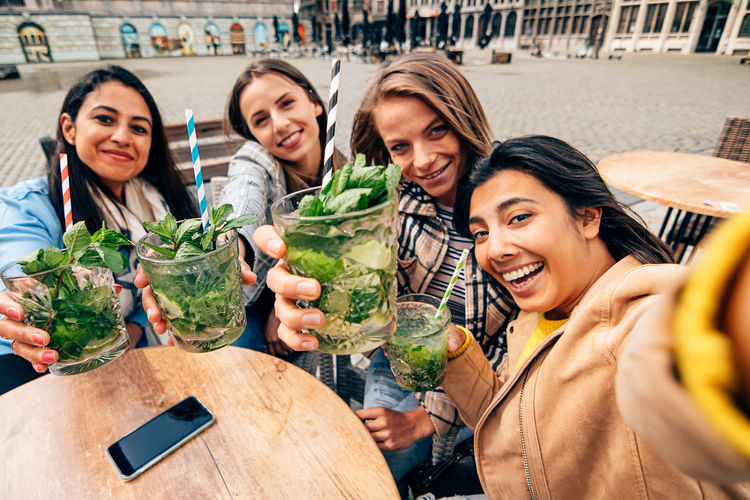 Mojito drinks held by a multiracial group of female friends taking a selfie while sitting at cafe